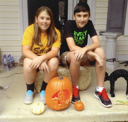 James and Anna Finneran pose with a carved pumpkin in preparation for Halloween festivities in October 2014.
