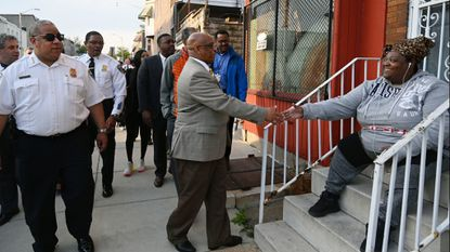 "Baltimore Police Commissioner Michael Harrison, left, watches as Baltimore Acting Mayor Bernard C. ""Jack"" Young stops to shake Tria Taylor's hand as city officials take a walking tour of the Broadway East neighborhood."