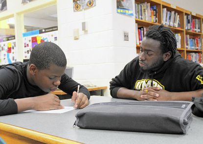 Jermaine Lee, 13, of Arbutus, does homework with the assistance of UMBC student JaQuon Epps, 23, during an afterschool session in the library at Arbutus Middle School on May 1.