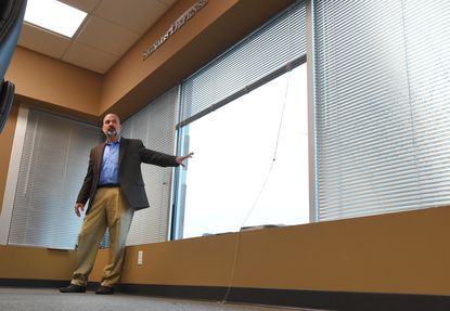 Owings Mills, MD -- Todd Gardner, the president of Signals Defense, shows one of a window that has been coated with one the company's protective films. Signals Defense has built a business selling building products that protect the Pentagon and other buildings from data leaks.