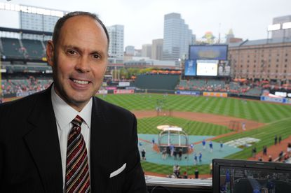 Ernie Johnson is seen in the TBS broadcast booth at Oriole Park at Camden Yards prior to game two of the ALCS playoff series against the Kansas City Royals.