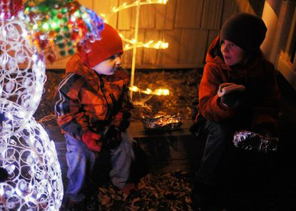 Connor Brown, 3, left, and his brother Jordan, 6, endured Saturday evening's chilly temperaturs as they waited outside Santa's house for his arrival at the Arbutus Town Hall on Nov. 24.