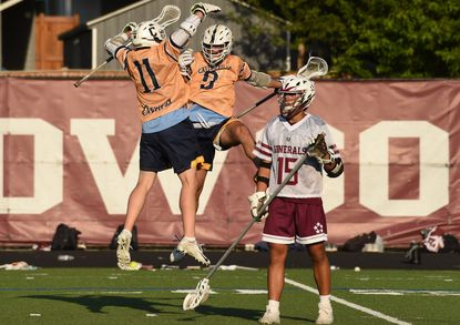 Catonsville goal scorer Byron Newman (11) celebrates with teammate Tyler Mikalaski in front of Towson's Tyler Stankoski during the Comets' 7-6 win over Towson on May 20.