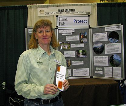 Paula Piatt at the Trout Unlimited booth at The Fly Show at Lancaster, Pa., with a brochure on Sportsmen Alliance for Marcellus Conservation.