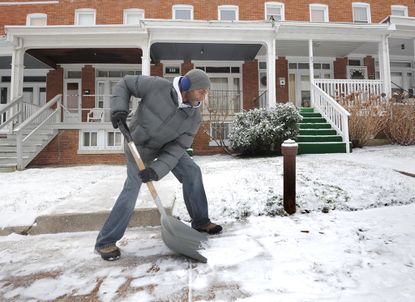 """LaMart Chase, 55, clears his and two of his neighbor's sidewalks in the 800 block of Belgian Ave. He explains that instead of each neighbor hiring someone to cut the grass or clear the snow, they take turns doing the work. """"That's what we do,"""" he said. Baltimore residents clean off cars and sidewalks after a covering of snow last night."""