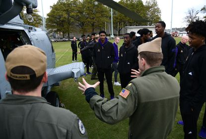 The East Carolina University men's basketball team checks out a MH-60S helicopter at the Naval Academy before the Veterans Classic last year. The event has been canceled with the college basketball season being delayed.
