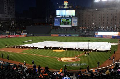 The grounds crew puts the tarp on the field for a rain delay before the game between the Orioles were to facethe Tampa Bay Rays at Oriole Park at Camden Yards on April 9, 2016 in Baltimore. The game waspostponed.