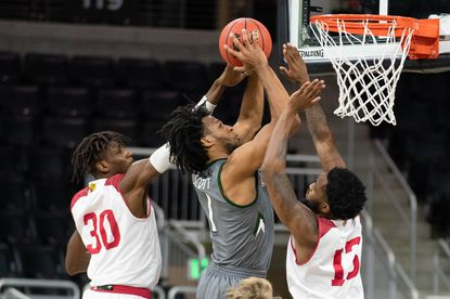 KaVaughn Scott scores two of his season-high 14 points on Monday night in Loyola University Maryland's 81-77 win over IUPUI as Zo Tyson (30) and Isaiah Williams (13) defend for the Panthers.