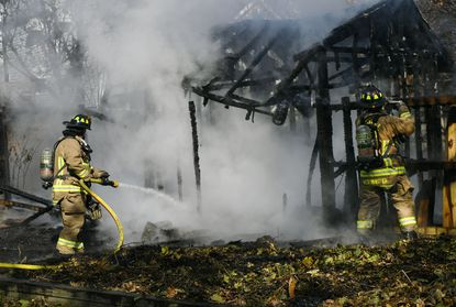 Firefighters work to extinguish a shed fire in the unit block of Liberty Street in Westminster Wednesday, Nov. 13, 2019.