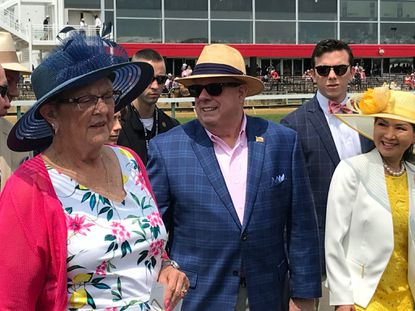 Governor Larry Hogan and wife Yumi Hogan (yellow hat) at the Preakness Stakes 2019.