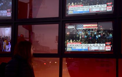 "A pedestrian walks past a display of tv screens in front of an office building in Hollywood, California on March 1, 2016 as results from ""Super Tuesday"" for the US presidential elections are flashed across the screen."