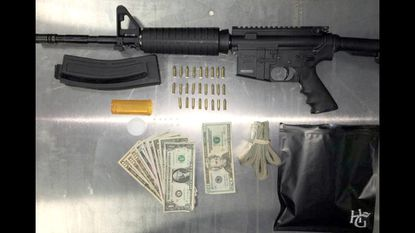 Money, firearms and illegal drugs are the items customarily confiscated when police crack down on criminal behavior like the above taken from a home on Edgevale Road in West Baltimore. Legalization would put an end to drug trafficking and, as a result, reduce gun violence, proponents claim. File.