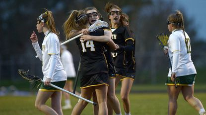 South Carroll's Mia MacKenzie celebrates with teammate Abbey Behn (14) after scoring in the second half of the Cavaliers' 9-7 win over Century in Eldersburg Tuesday, April 17, 2018.