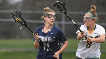 Manchester Valley's Mackenzie D'Anthony, left, controls the ball with Century's Rachel Rubenstein applying defensive pressure during a girls lacrosse game at Century High School on Monday, April 8.