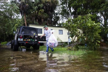 Mitchell Pope tries to salvage what he can from his mobile home after the Wakulla and St. Marks rivers overflowed in St. Marks, Fla.