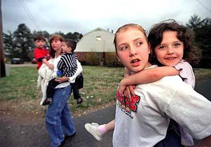 Alyssa Kreinschroeder, with sister Madeline on her back, helps out her mom, Kris, with the family, including twins Mathias and Hayden (background).