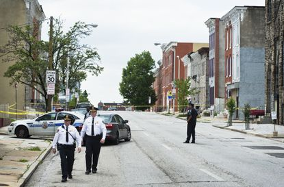 City police officers at a crime scene in May.