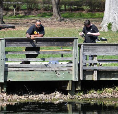 Jemuel Walls, left, keeps a close eye on his fishing line as he and a friend Shawn Monaghan, right, spend some time fishing at Friends Community Park in Forest Hill Monday, April 5, 2021. Recently visitors have complained about overgrown vegitation, trash and a lack of water in the popular Forest Hill park.