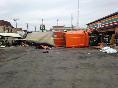 A tractor-trailer overturned damaging a bus stop, sending two people to the hospital.