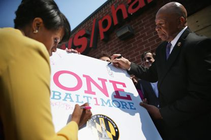 BALTIMORE, MD - MAY 07: Mayor Stephanie Rawlings-Blake (L) and U.S. Rep. Elijah Cummings (D-MD) (R) sign a poster during a news conference in front of the burned CVS in the Sandtown neighborhood May 7, 2015 in Baltimore, Maryland. Community leaders joined the mayor to kick off the One Baltimore campaign, a public-private initiative to support efforts to rebuild communities and neighborhoods after the riot that was caused by the death of Freddie Gray. (Photo by Alex Wong/Getty Images) ORG XMIT: 553072105