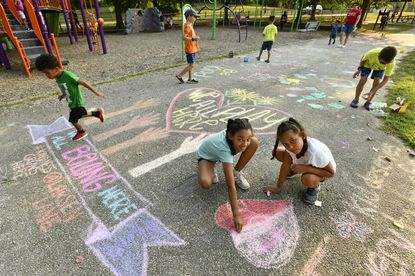 """Samara Stephan, 9, center, and Myka Frazier, 7 1/2, right, both of Crofton, add a heart to the messages of love and inclusion at a """"Kindness Grows Here"""" event at Bell Branch Park. Kristen Caminiti, founder of Kindness Grows Here, helped put together the gathering for the Crofton, Odenton and Gambrills communities after Kia Rorie of Gambrills wanted a positive community response to bigotry experienced by her two Black children at the park earlier this month. (Parents gave permission for photo.) July 28, 2021 p1"""