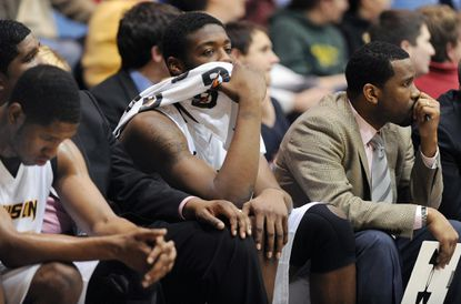 Towson players Erique Gumbs (head down), Jervon Pressley and coordinator of basketball operations Duane Simpkins react as the clock drops below a minute in the Tigers' 66-49 home loss to William & Mary Wednesday night.