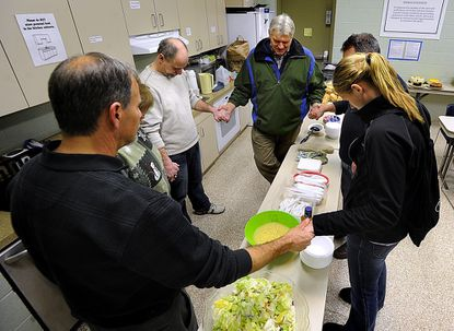 Ralf Nies, center, pastor of Grace Fellowship Chapel in Westminster, says a blessing with volunteers, from left, Carl Reimer, LuAnn Gamber, Sean Staley, Keith Jarrin and McDaniel College junior Sam Wilson, who is interning at HSP, after preparing supper at the Carroll County Cold Weather Shelter in Westminster Thursday.