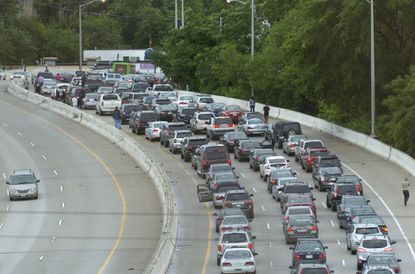 Traffic backs up on the southbound JFX after a Baltimore police officer and a civilian were injured in an accident Friday evening on the Jones Falls Expressway, with the civilian thrown off the highway into the Jones Falls below.