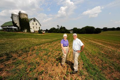 Lambert and Marjorie Cissel pose for a portrait on their 180-acre farm in Lisbon. The Cissels worry a new state law will force them to develop their land to avoid losing its value.