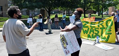 A truck driver trying to get in to the BRESCO facility speaks with Shashawnda Campbell, with the South Baltimore Community Land Trust. She is one of the demonstrators at the SB7 Coalition Inc. rally blocking the entrance. Protestors want to shutdown the BRESCO trash incinerator and advocate for building a zero waste infrastructure. July 29, 2020.