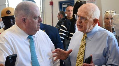 Maryland Governor Larry Hogan, left, talks with BSC America Chairman and CEO Raymond Nichols, right, as they tour the auction floor during the Governor's visit to the year-old Bel Air Auto Auction facility in Belcamp Thursday afternoon.