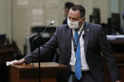 In this Monday June 15, 2020 file photo, a podium used in the California State Assembly is disinfected at the Capitol in Sacramento, California. The state will require its government employees and all health care workers to show proof of COVID-19 vaccination or get tested weekly in an effort to slow the rising coronavirus infections, mostly among the unvaccinated. The new rule will take effect next month. (AP Photo/Rich Pedroncelli, File)