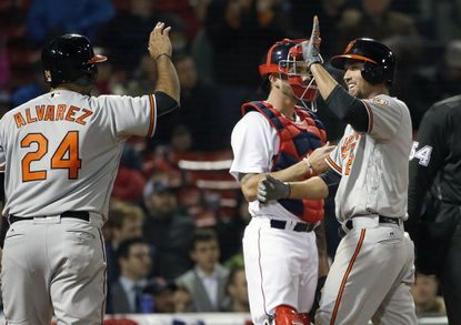 Orioles' J.J. Hardy, right, celebrates his two-run home run that also drove in Pedro Alvarez (24) in front of Boston Red Sox's Blake Swihart, behind, during the seventh inning in Boston, Tuesday, April 12, 2016.