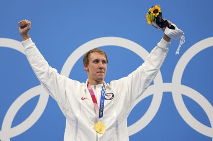 Gold medalist Chase Kalisz celebrates on the podium after winning the men's 400-meter individual medley at the 2020 Summer Olympics, Sunday, July 25, 2021, in Tokyo, Japan. (AP Photo/Matthias Schrader)