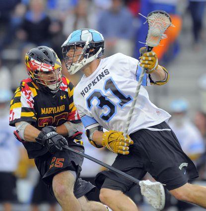 Maryland's Taylor Morgan defends against Johns Hopkinss midfielder John Ranagan in the second quarter of NCAA men's lacrosse action at Homewood Field.