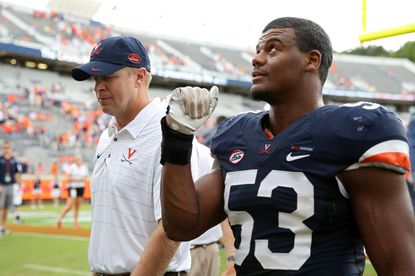 Virginia linebacker Micah Kiser pumps his fist as he walks off the field with head coach Bronco Mendenhall after a win over Connecticut at Scott Stadium on September 16, 2017 in Charlottesville, Va.