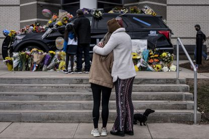 Sarah O'Keefe and Maura Kieft pay their respects to Officer Eric Talley, who was killed after a gunman opened fire at a King Sooper's grocery store on March 23, 2021 in Boulder, Colorado. (Photo by Chet Strange/Getty Images)