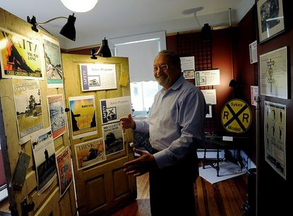 """Mark Fraser, curator of the Sykesville Gate House History Museum shows off a display of railroad safety posters in the museum's new exhibit """"Gone Off the Rails -- When Safety Fails"""" that chronicles the history of regional train accidents and railroad safety in Sykesville Tuesday, Sept. 25, 2012."""