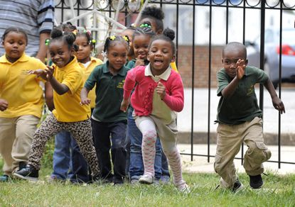 Students at Little Flowers Child Development Center laugh and play during a morning on the playground. Some of the children who attend the Baltimore school are exposed to violence in their neighborhood - an exposure scientists increasingly realize can cause health impacts.