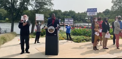 Protesters hold up signs advocating to end Howard County's contract with ICE at County Executive Calvin Ball's press conference Tuesday.