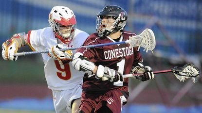 Calvert Hall senior longstick Evan Connell, left, attempted to slow down Conestoga's Bradlee Lord in the Cardinals' 11-10 loss Friday night in Towson.