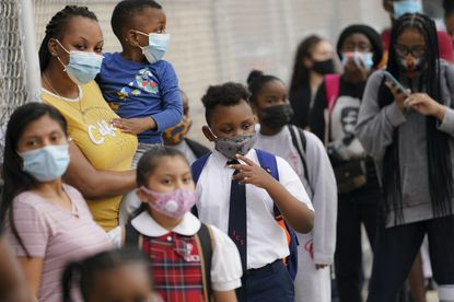 FILE - In this Sept. 9, 2020, file photo, students wear protective masks as they arrive for classes at the Immaculate Conception School while observing COVID-19 prevention protocols in The Bronx borough of New York. Schools and camps across the county are making plans to help kids catch up academically this summer after a year or more of remote learning for many of them. (AP Photo/John Minchillo, File)