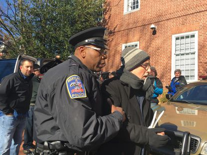 Mike Tidwell of the Chesapeake Climate Action Network is guided to a police SUV by a Maryland Capitol Police officer at the State House complex in Annapolis on Thursday morning. He was among several anti-fracking demonstrators who were arrested for blocking the entrance to a public building. The activists hoped their arrests would draw attention to the need to ban the controversial form of drilling for natural gas.