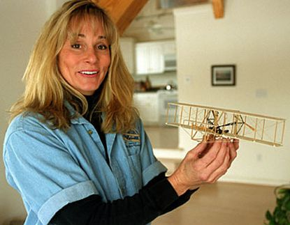 At her home in Trappe, Md., on the Eastern Shore, Terry Queijo, a pilot with American Airlines, holds a model of the 1903 Wright Flyer. Three others are vying for the honor to pilot the re-created plane.