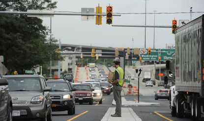 A worker waits to cross Russell Street across near the Horseshoe Casino. Congested traffic moves slowly during the rush hour near the casino, which is under construction.