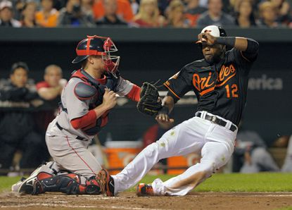 Alejandro De Aza slides into home plate in a game against the Boston Red Sox in September.