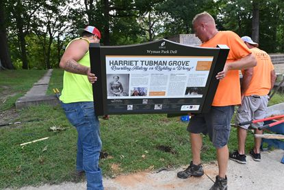 From left, Mike Aldi and Taylor Schmidt, installers with Color-Ad Signs and Exhibits, work to place one of two signs in Wyman Park Dell naming a section of the park Harriet Tubman Grove. The Friends of Wyman Park Dell are placing the markers, one honoring Tubman and the other telling the story of the monument, near the site of the Jackson and Lee Monument which was removed in 2017. September 14, 2020.
