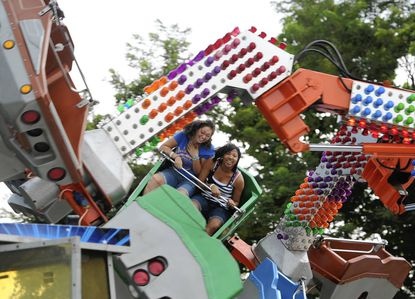 Breonna Herold, 16, left, and Jerosha Herold, 17, of Bel Air, ride the Orbiter at the carnival Wednesday.