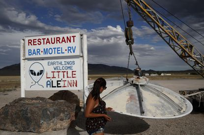 """Grace Capati looks at a UFO display outside of the Little A'Le'Inn, in Rachel, Nev., the closest town to Area 51. The U.S. Air Force has warned people against participating in an internet joke suggesting a large crowd of people """"storm Area 51,"""" the top-secret Cold War test site in the Nevada desert."""