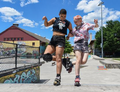 Ace Thompson, left, clicks heels with Tula Honkala as they roller skate at the Skatepark of Baltimore in Hampden's Roosevelt Park on Wednesday. 06.23.21.